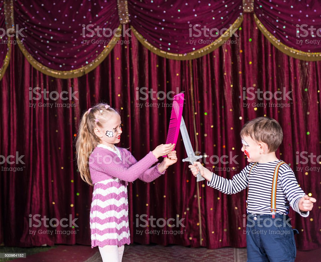 Young Clowns Having Prop Sword Fight on Stage stock photo