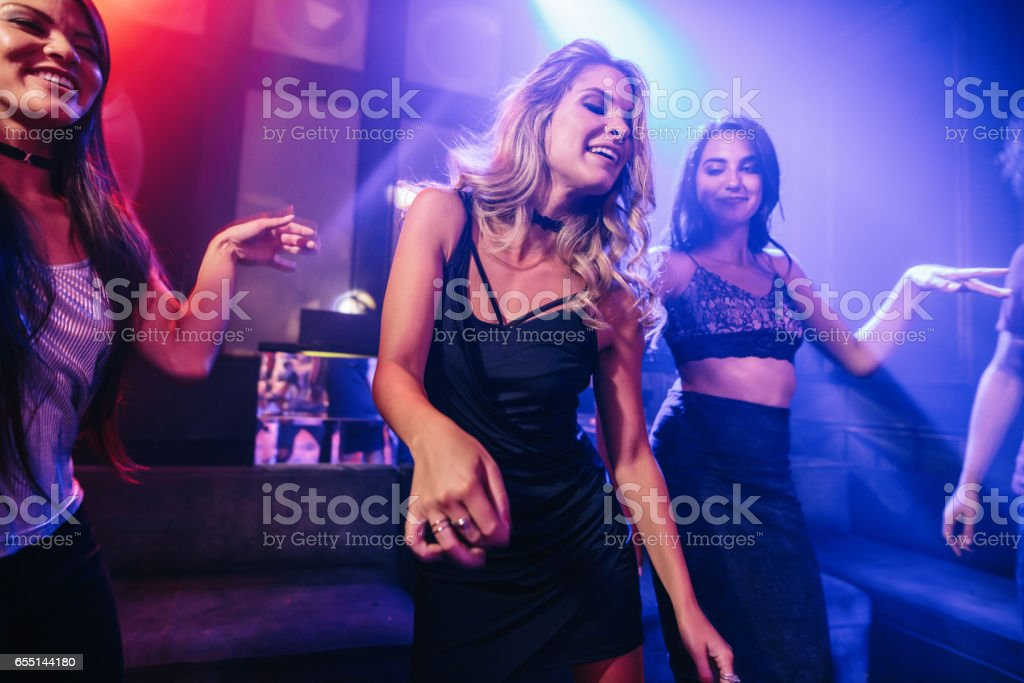 Young clubber dancing surrounded by her friends stock photo
