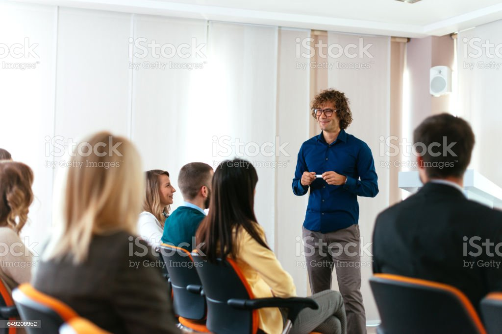 Young coach holding speech on conference with many young participants stock photo