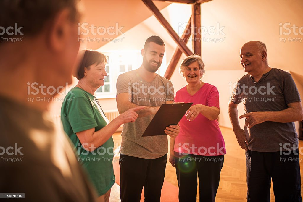 Young coach making an exercise plan for group of seniors. stock photo