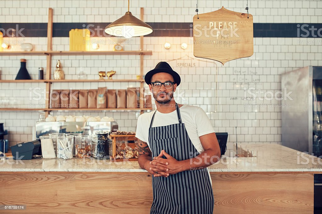 Young coffee shop owner standing at the counter stock photo