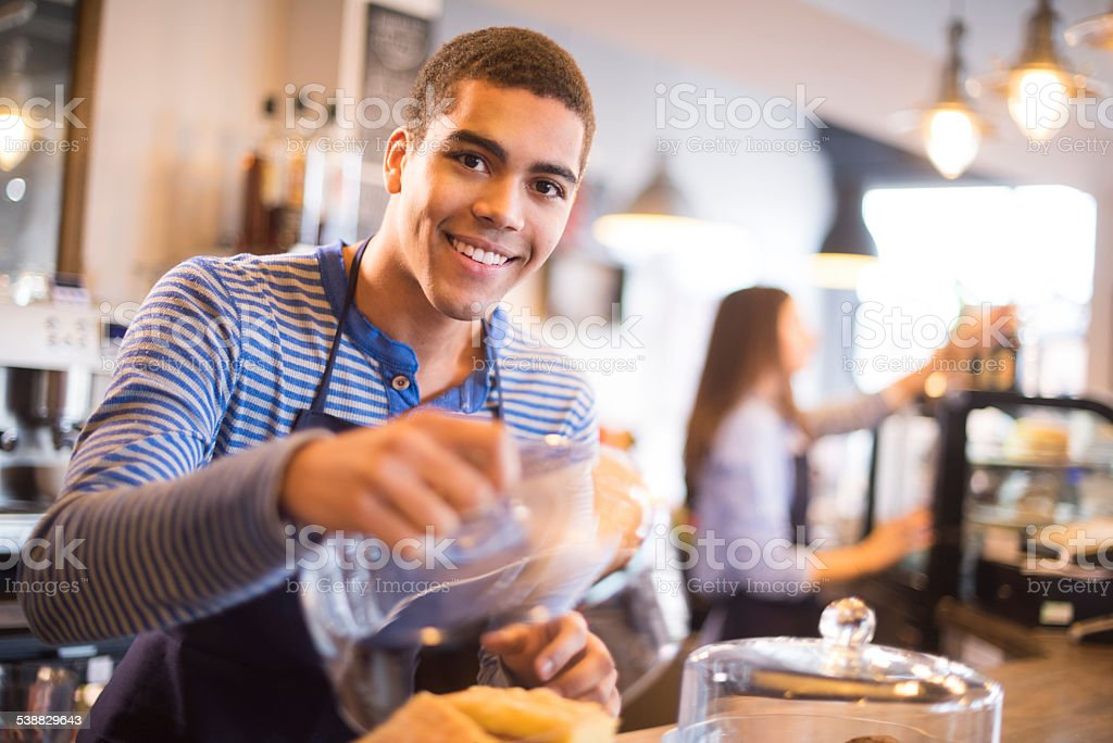 young coffee shop waiter shows off his flapjacks stock photo