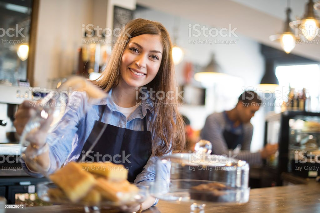 young coffee shop waitress shows off her flapjacks stock photo