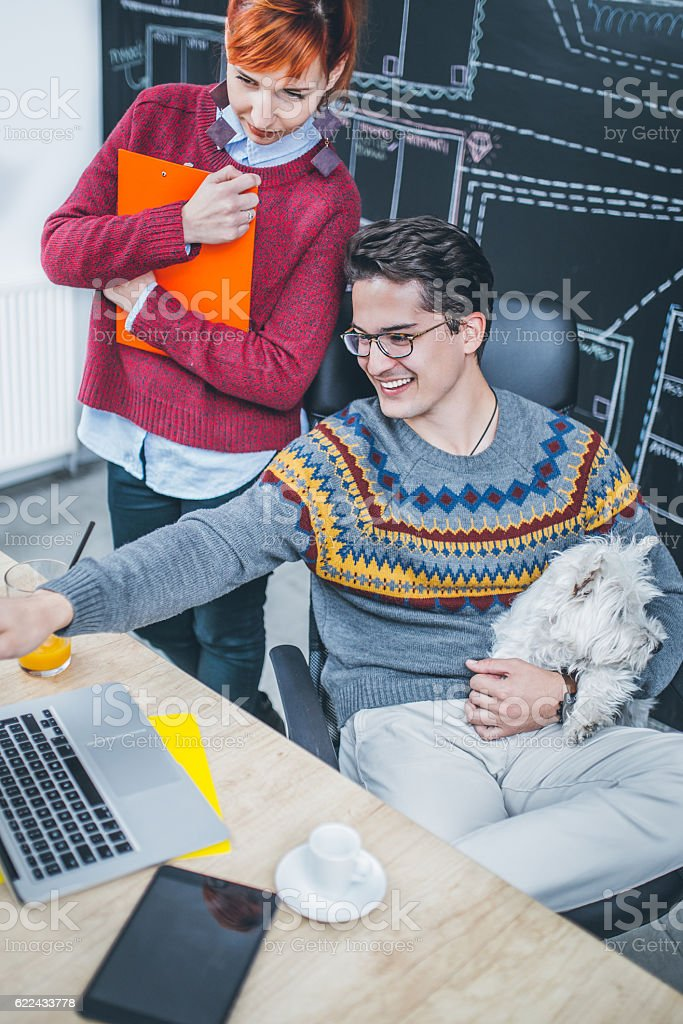 Young colleagues analyzing work results together stock photo