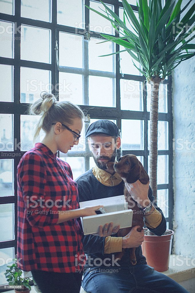 Young colleagues discussing a work matter near the window. stock photo