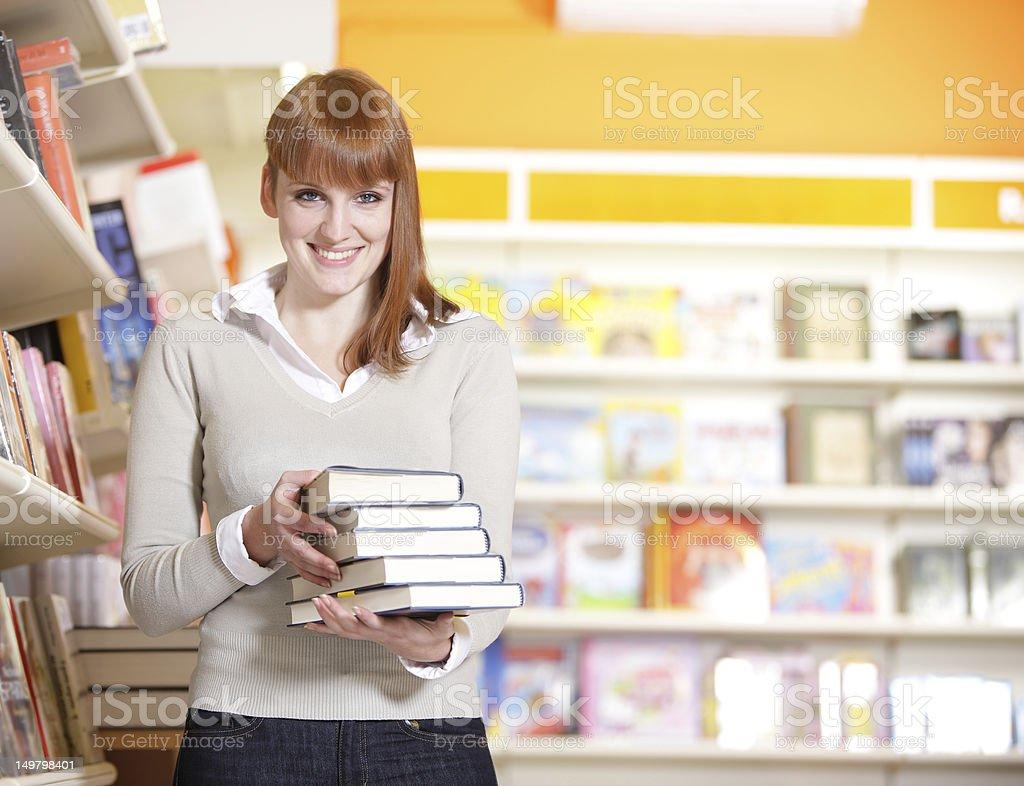Jeune étudiante dans une bibliothèque de Collège photo libre de droits