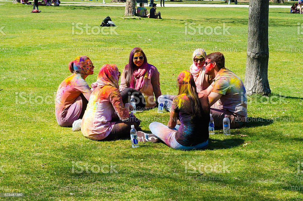 Young colorful people talking on grass Festival of Colours stock photo