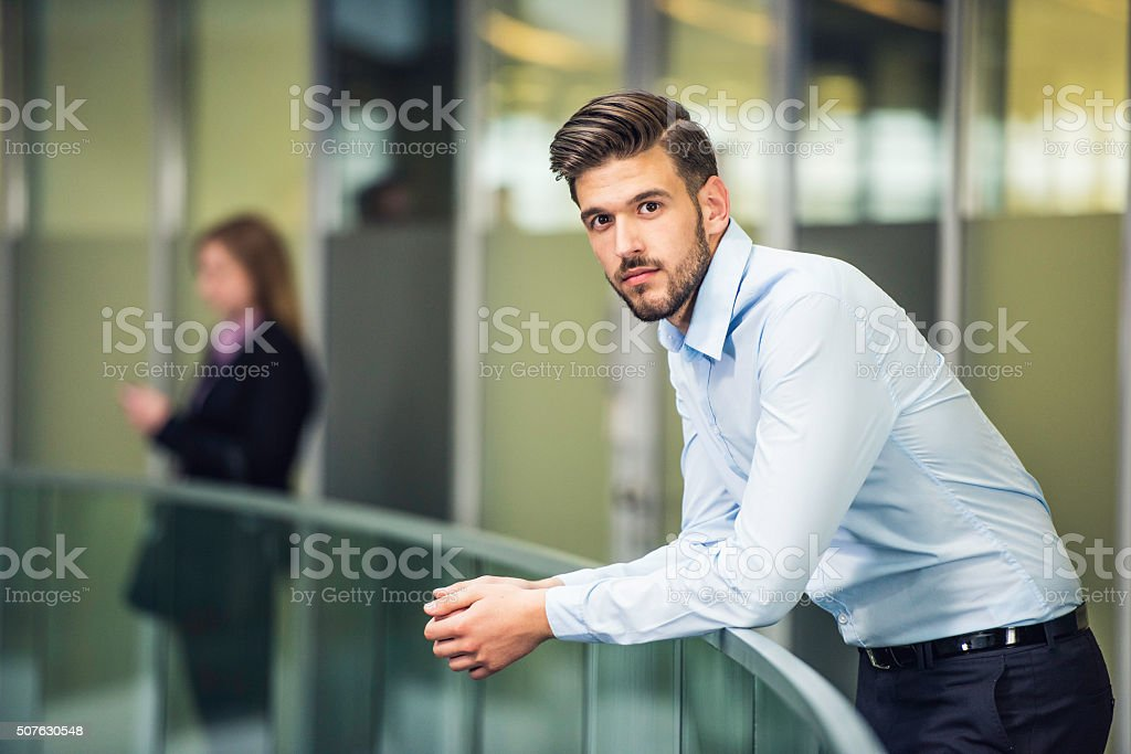 Young commercialist during break in office hallway stock photo