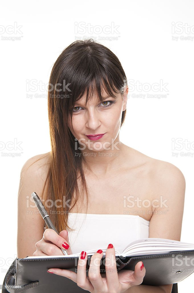 Young concentrated business woman holding notepad and a pen royalty-free stock photo