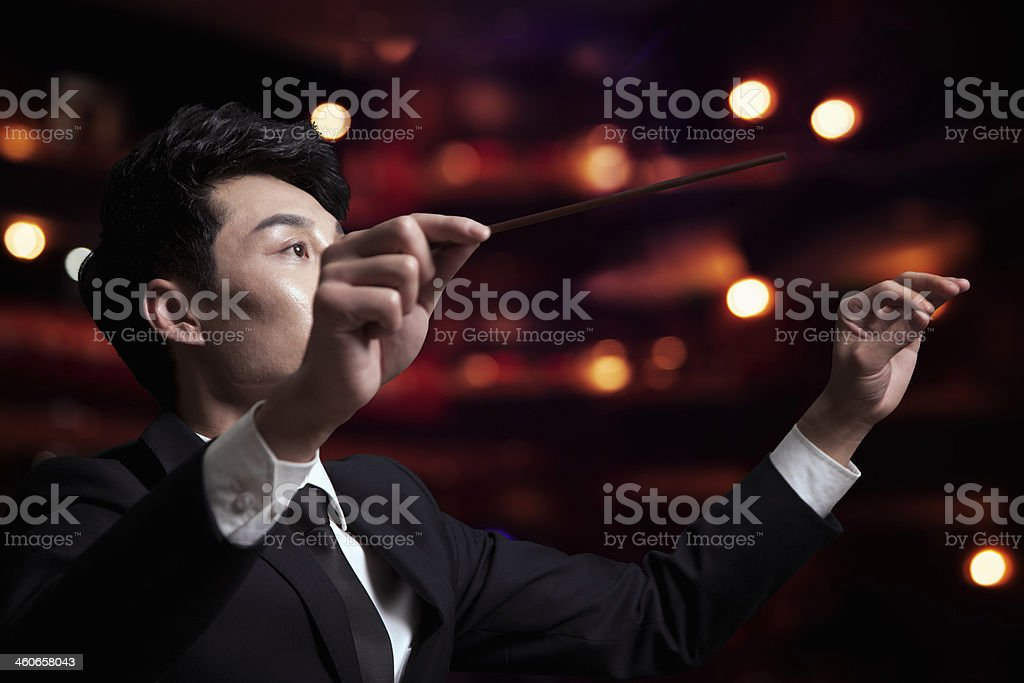 Young conductor with baton raised at a performance stock photo
