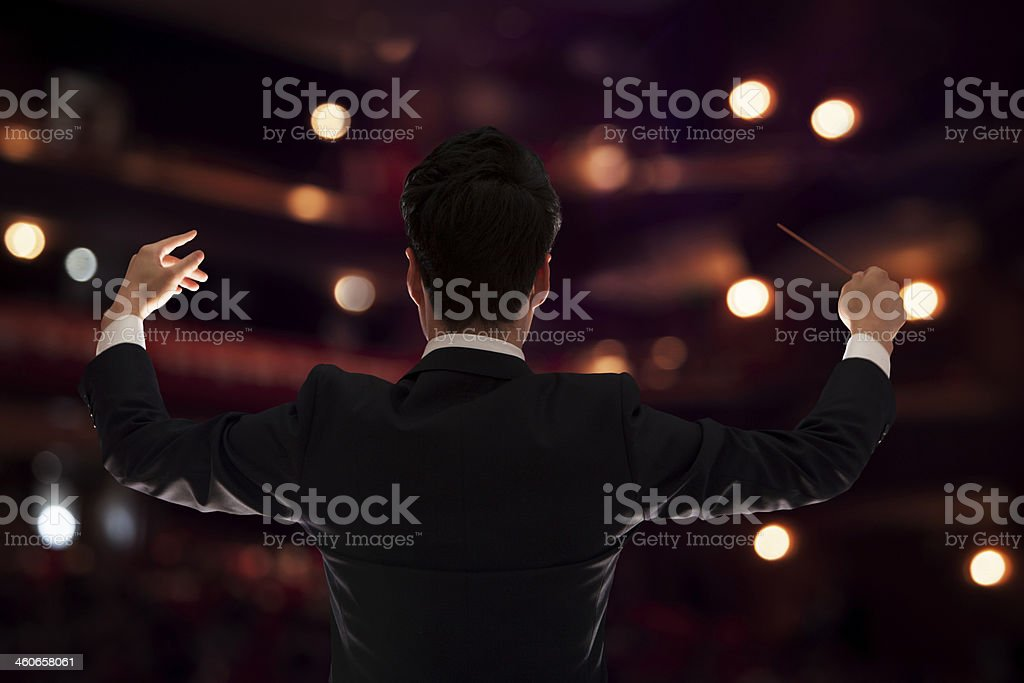 Young conductor with baton raised at a performance, rear view stock photo
