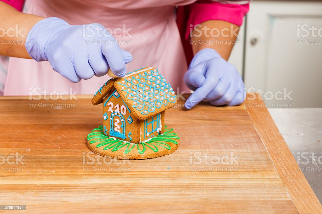 Young confectioner decorating gingerbread house in the kitchen stock photo