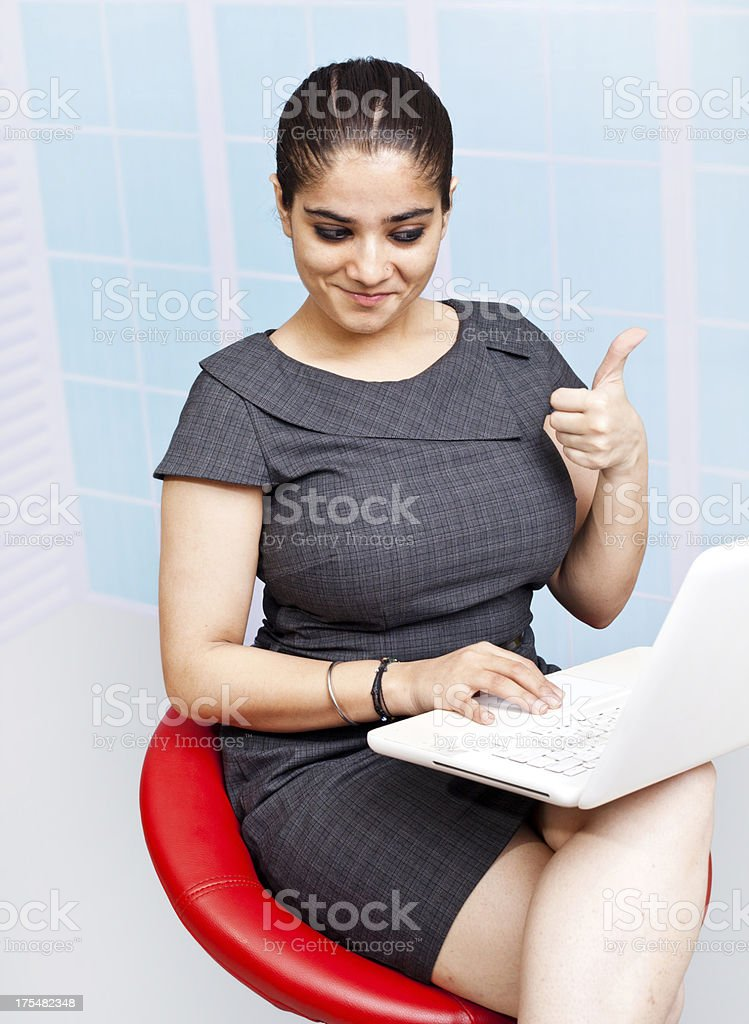 Young Confident Attractive Indian Businesswoman with Thumbs Up Using Laptop royalty-free stock photo