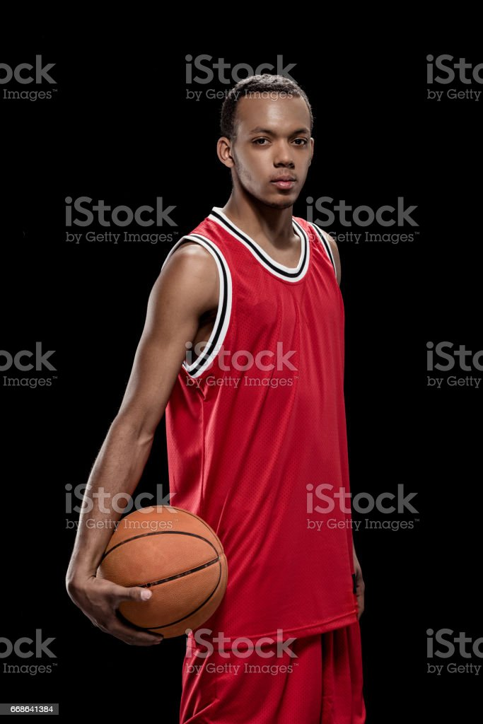 Young confident basketball player standing with ball and looking at camera stock photo