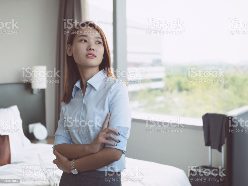 young confident business woman with arms crossed standing in hotel...