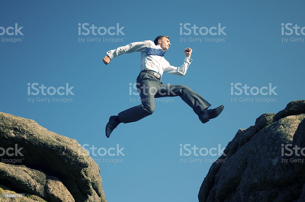 Young Confident Businessman Jumping in Blue Sky Between Boulders royalty-free stock photo