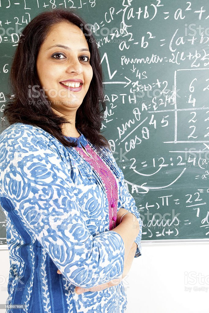 Young Confident Cheerful Indian Mathematics Teacher in a Classroom royalty-free stock photo