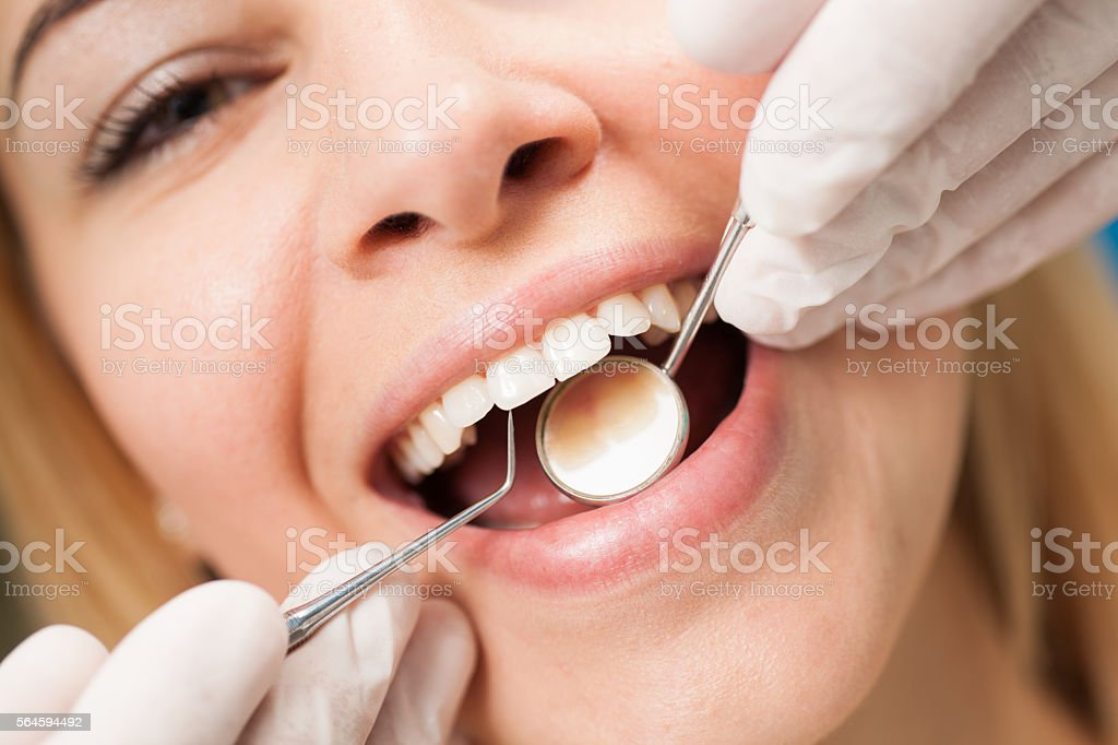 Young confident woman at  dentist's office having routine checkup. stock photo