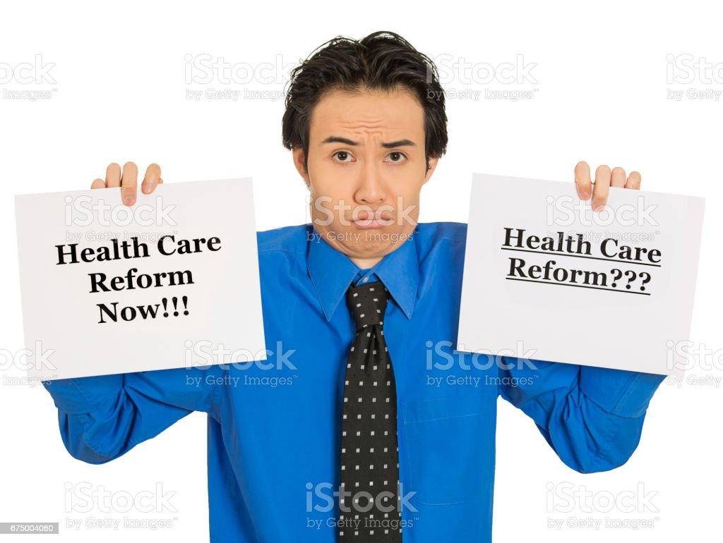 young confused business man holding healthcare reform sign puzzled uncertain undecided stock photo