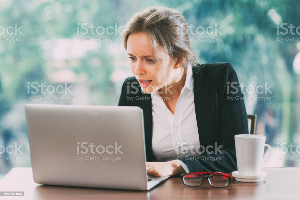 Young Confused Businesswoman Working on Laptop stock photo