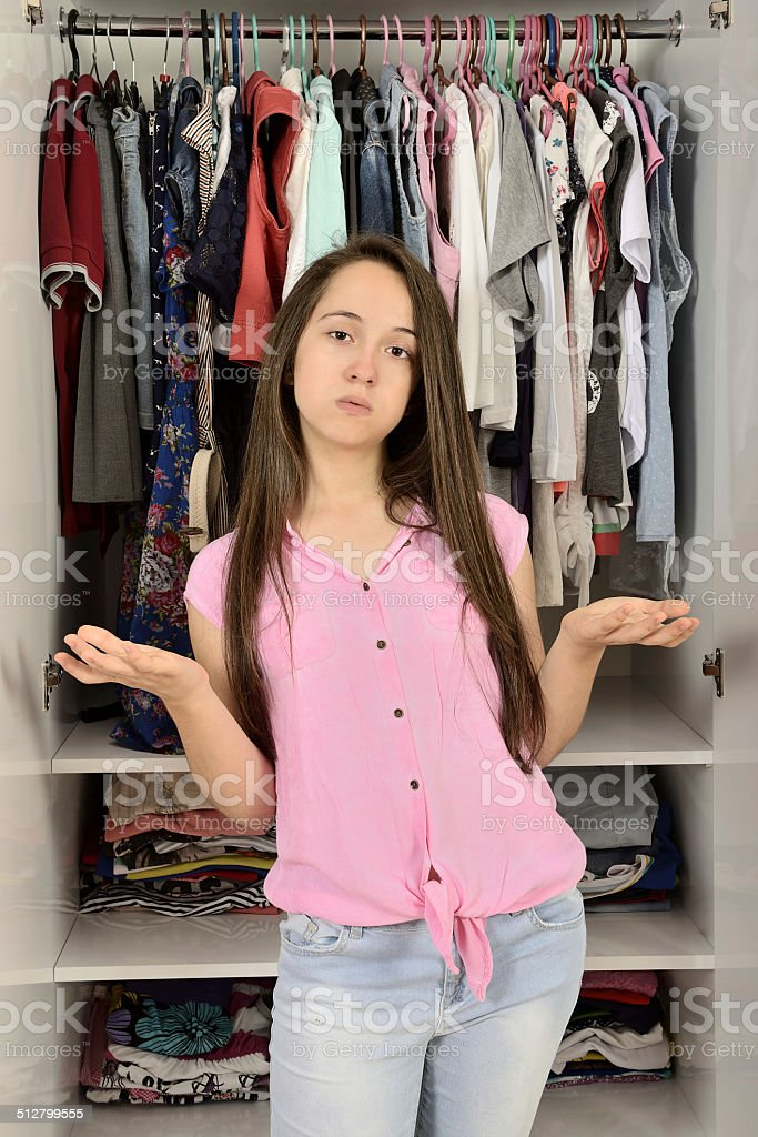 Young confused girl thinking in front of a wardrobe stock photo
