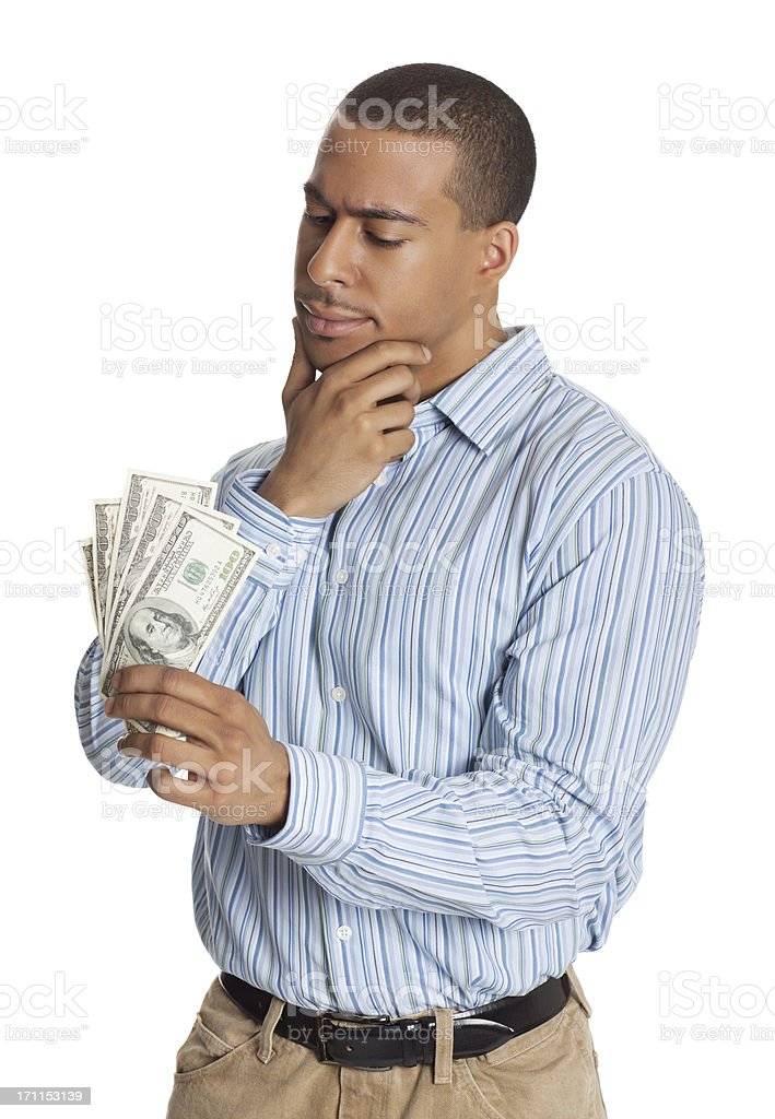 Young confused male looking at fan of dollar bills royalty-free stock photo