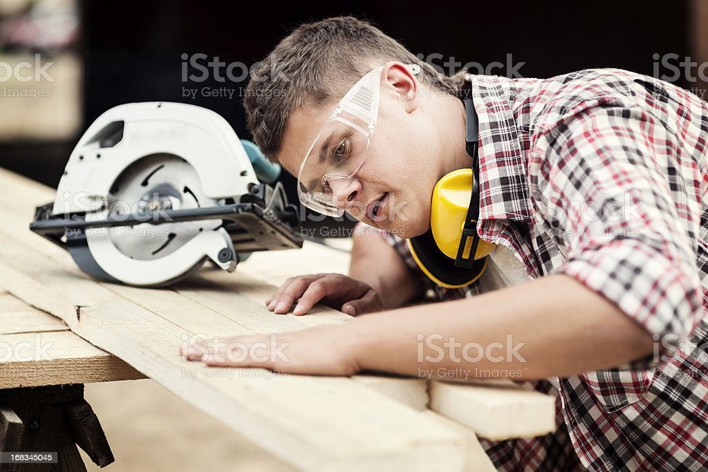 Young construction worker cutting wood stock photo
