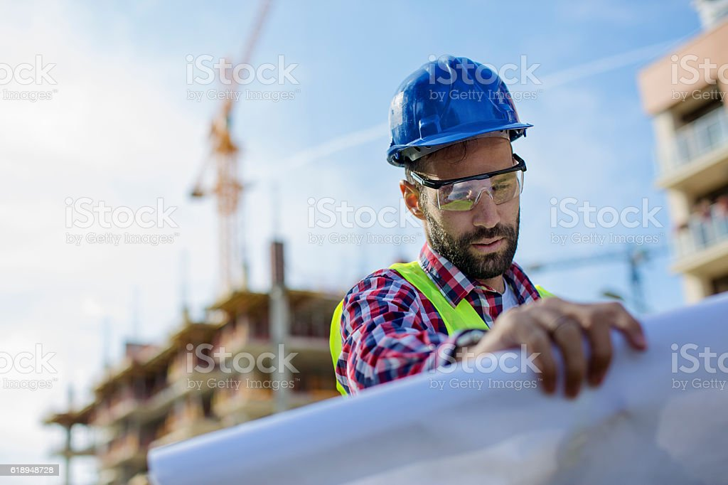 Young construction worker looking at blueprints stock photo