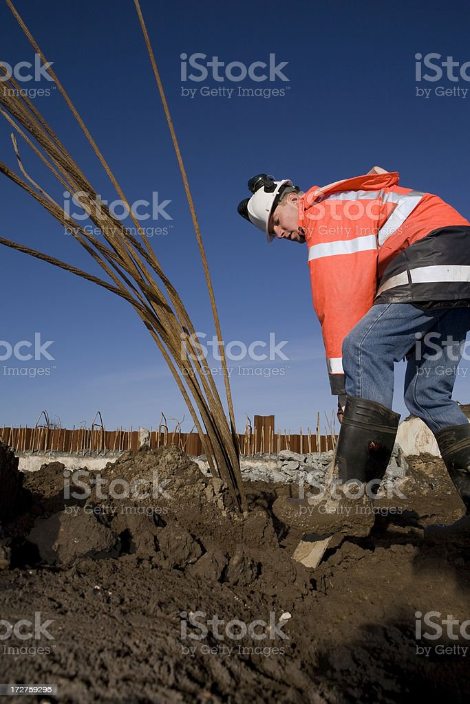 Young construction worker on a building pit, digging with shovel royalty-free stock photo