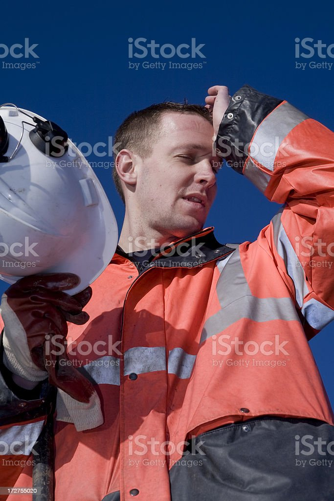 Young construction worker on a building pit, tired stock photo