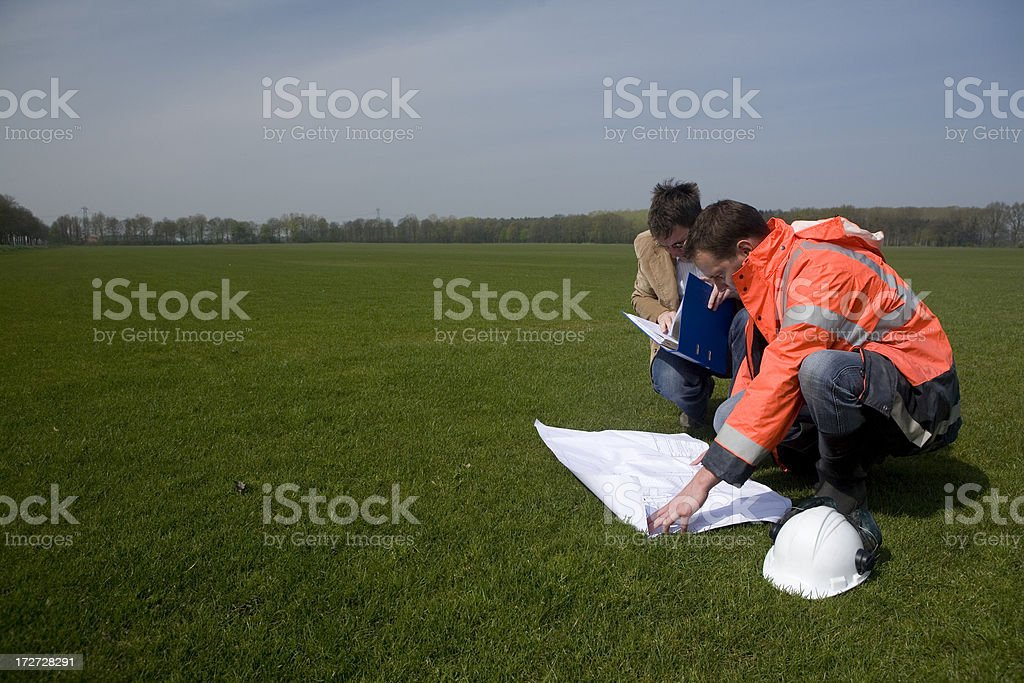 Young construction worker on a building pit, with his manager royalty-free stock photo