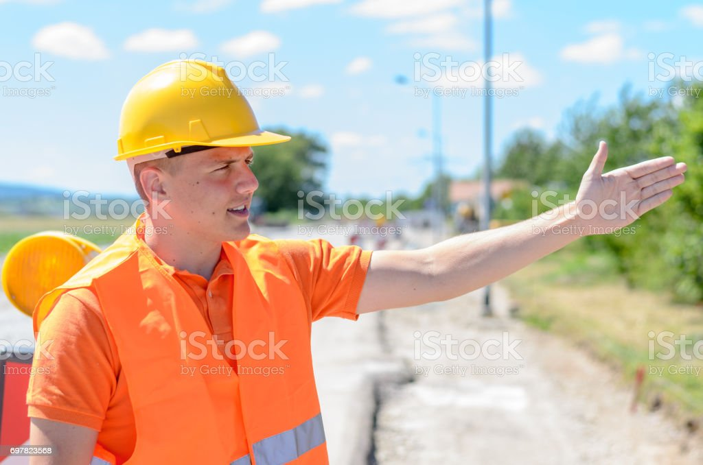 Young construction worker signalling with his hand stock photo