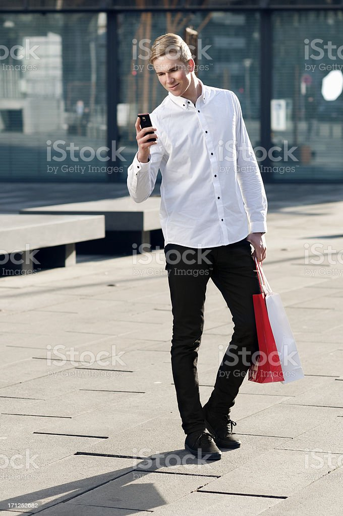 Young consumer with smartphone and shopping bags royalty-free stock photo