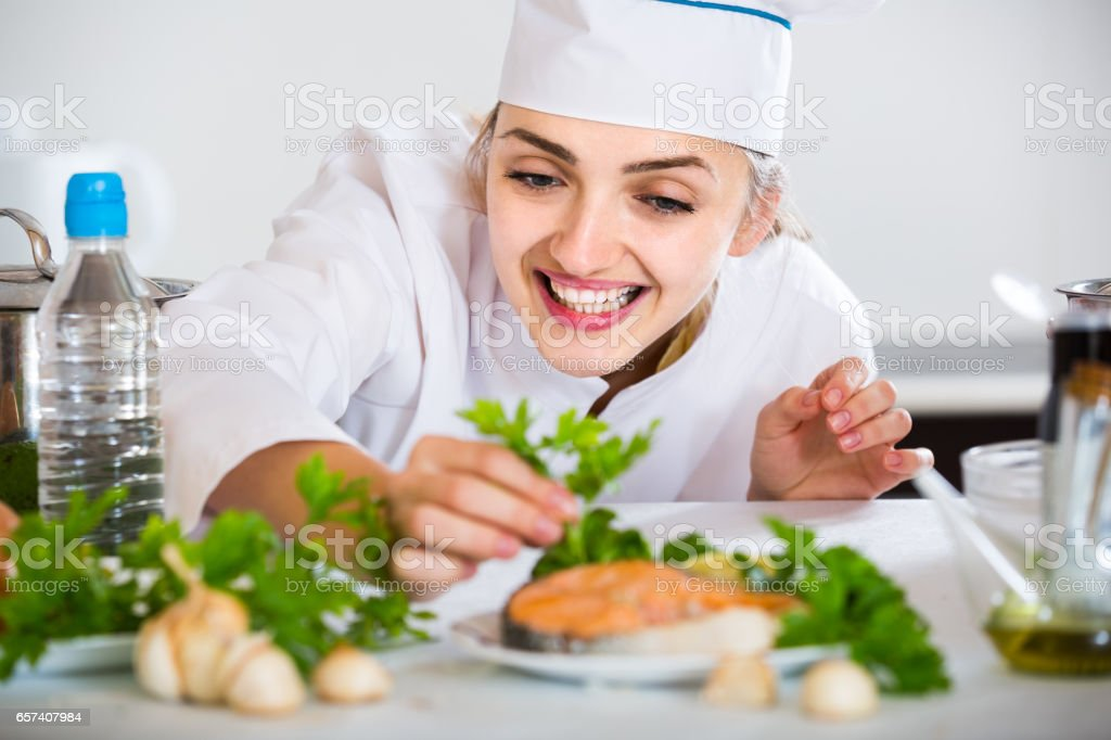 young cook with prepared salmon in professional kitchen stock photo