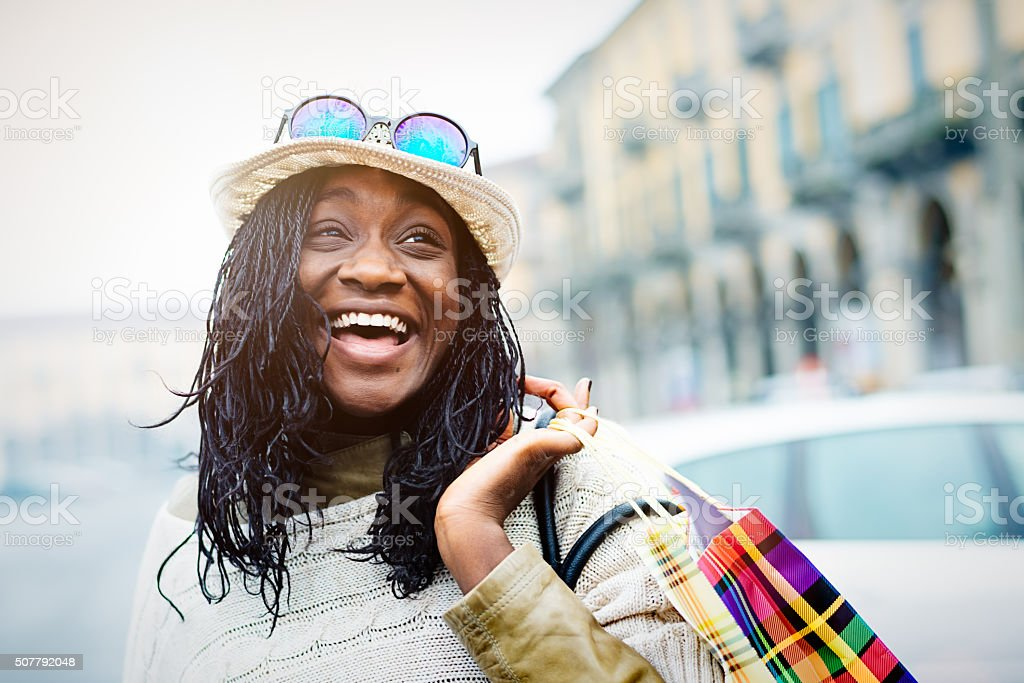 Young cool African woman with shopping bags on the street stock photo