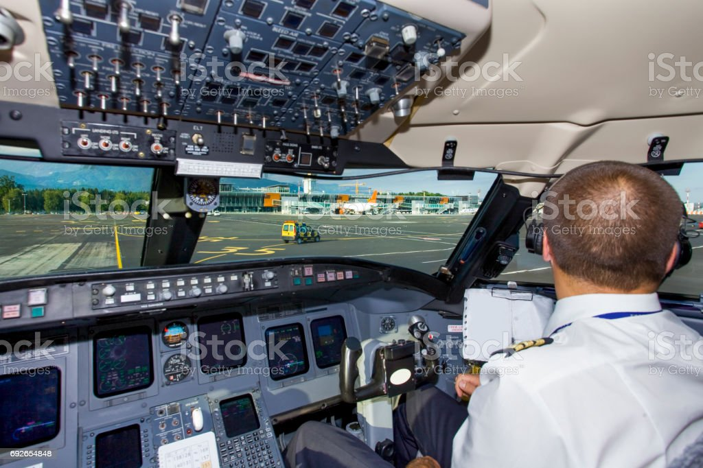 Young co-pilot at work in a cabin of commercial jet stock photo