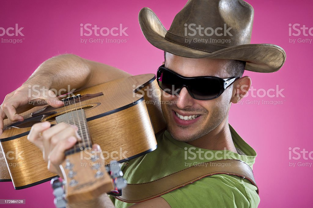 young country singer with guitar  portrait  pink background stock photo