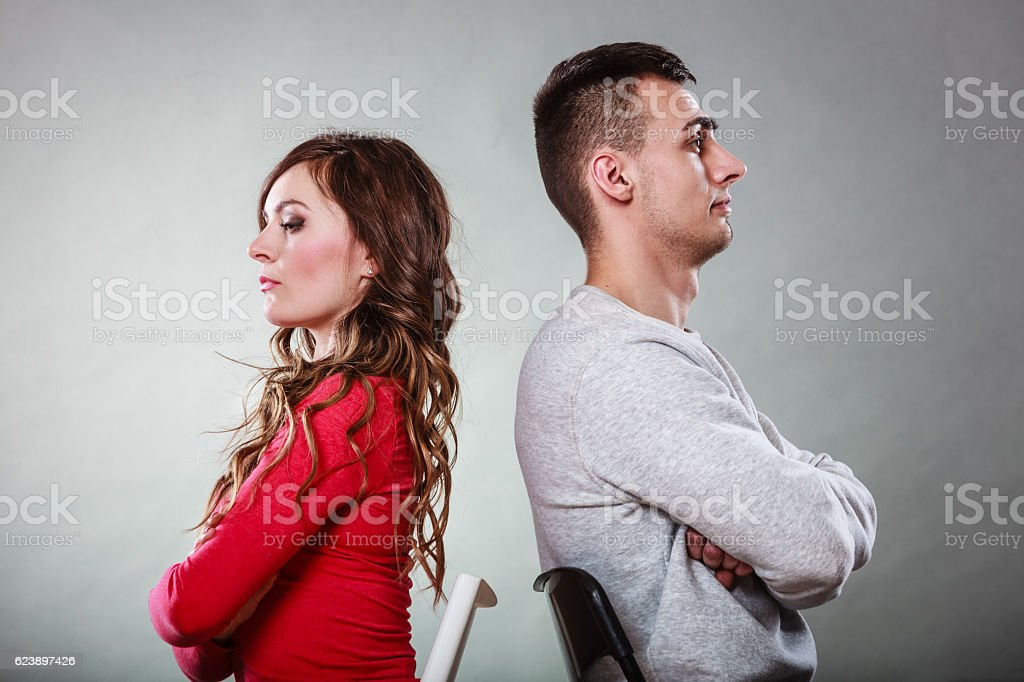 Young couple after quarrel sitting back to back stock photo