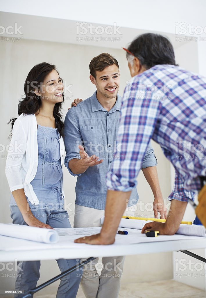 Young couple and architect discussing home renovation plan royalty-free stock photo