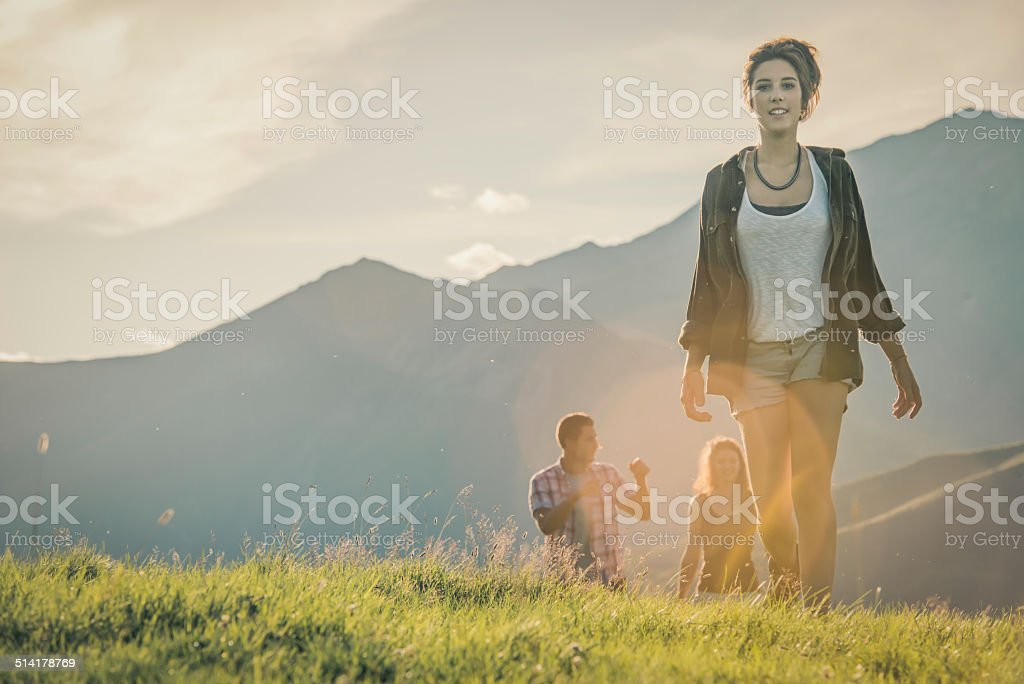 Young couple and friend walk on mountain in sunny day stock photo