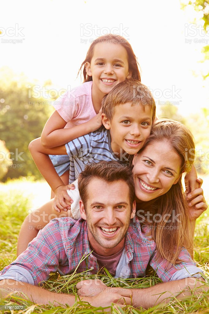 Young couple and kids having fun together outdoors stock photo