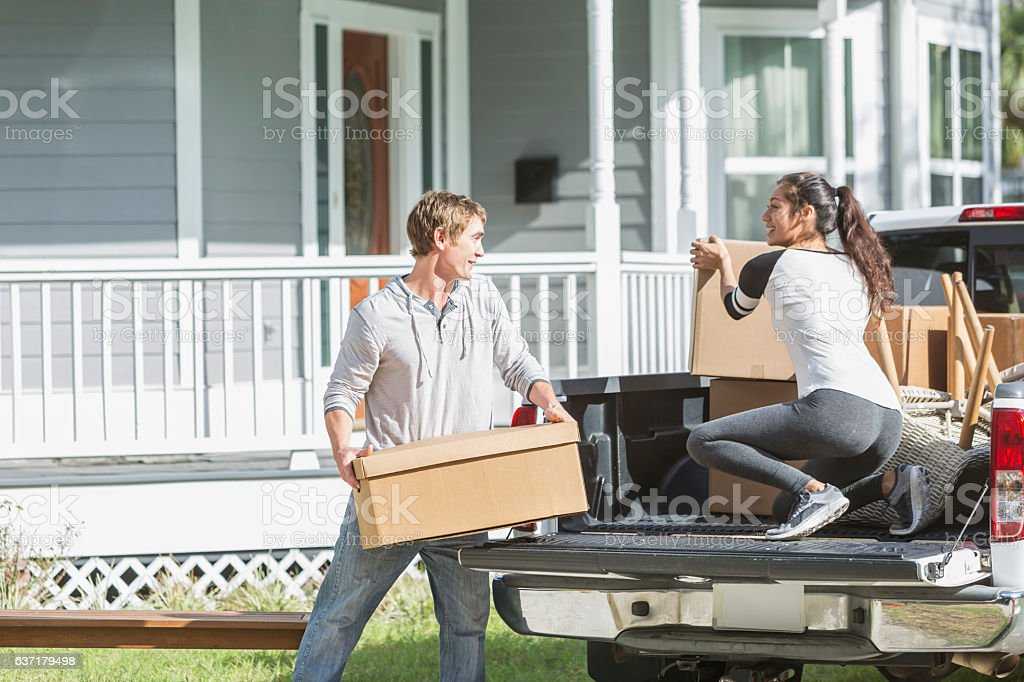 Young couple and pickup truck loaded with boxes and furniture stock photo