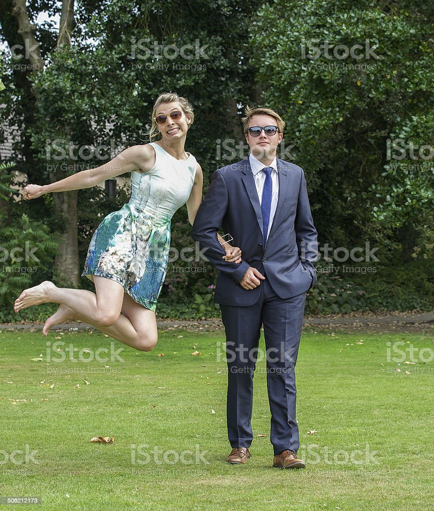 Young couple, arm in arm, woman jumping stock photo