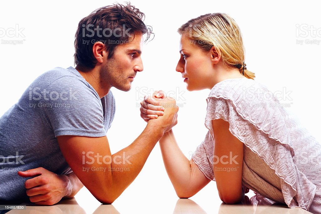 Young couple arm wrestling against white background stock photo