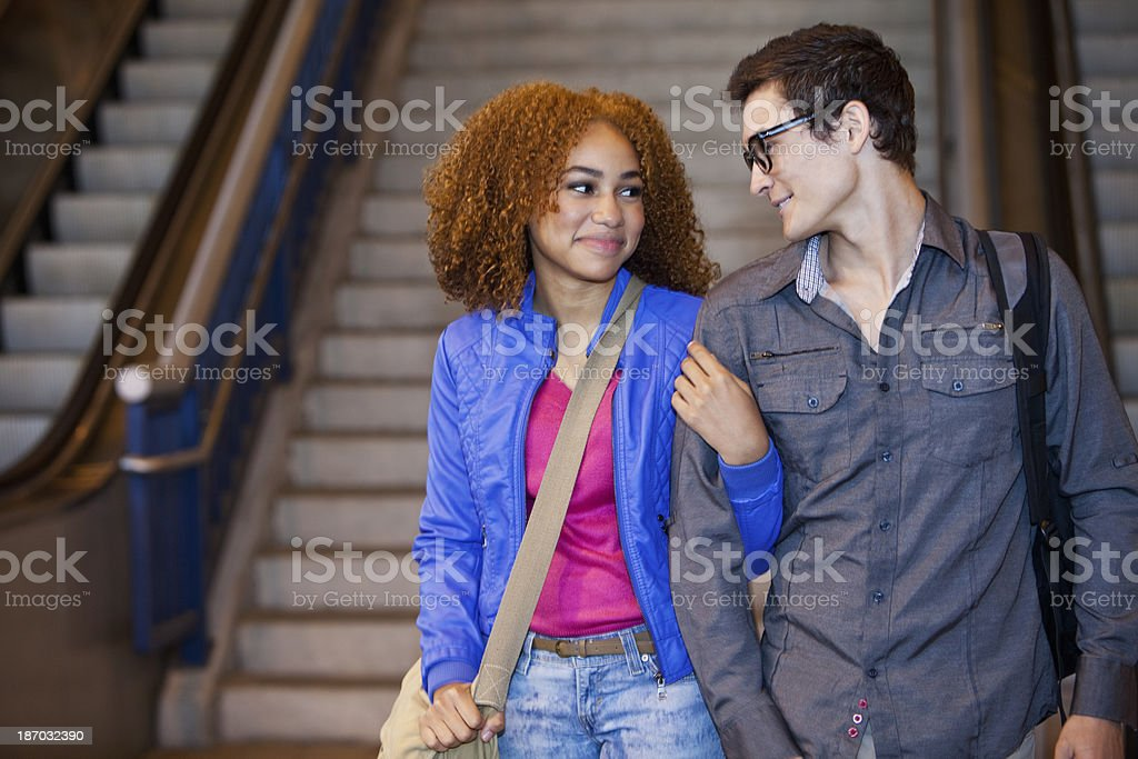 Young couple at bottom of stairs stock photo