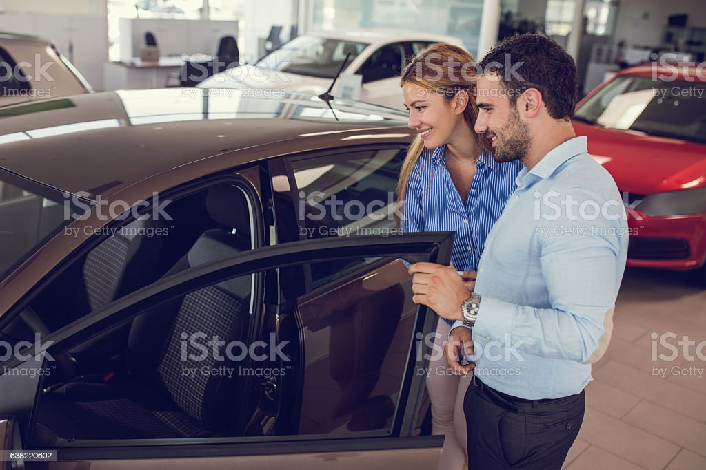 Young couple at car dealership looking at new car together. stock photo