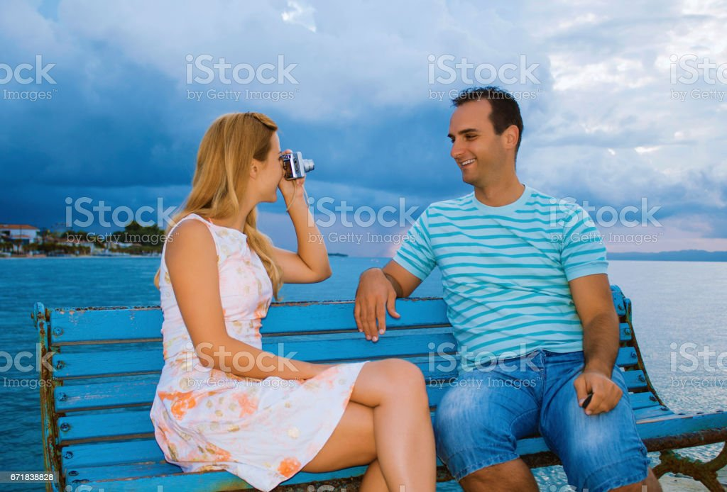Young couple at dock photographing stock photo