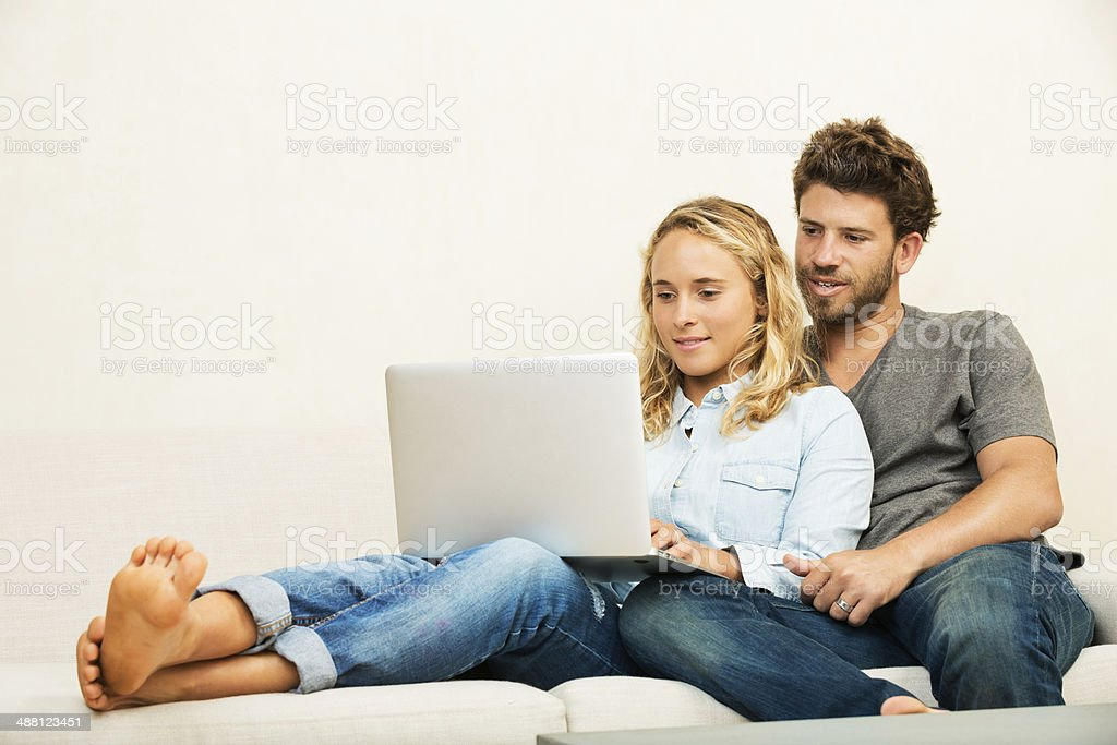 Young couple at home using laptop stock photo