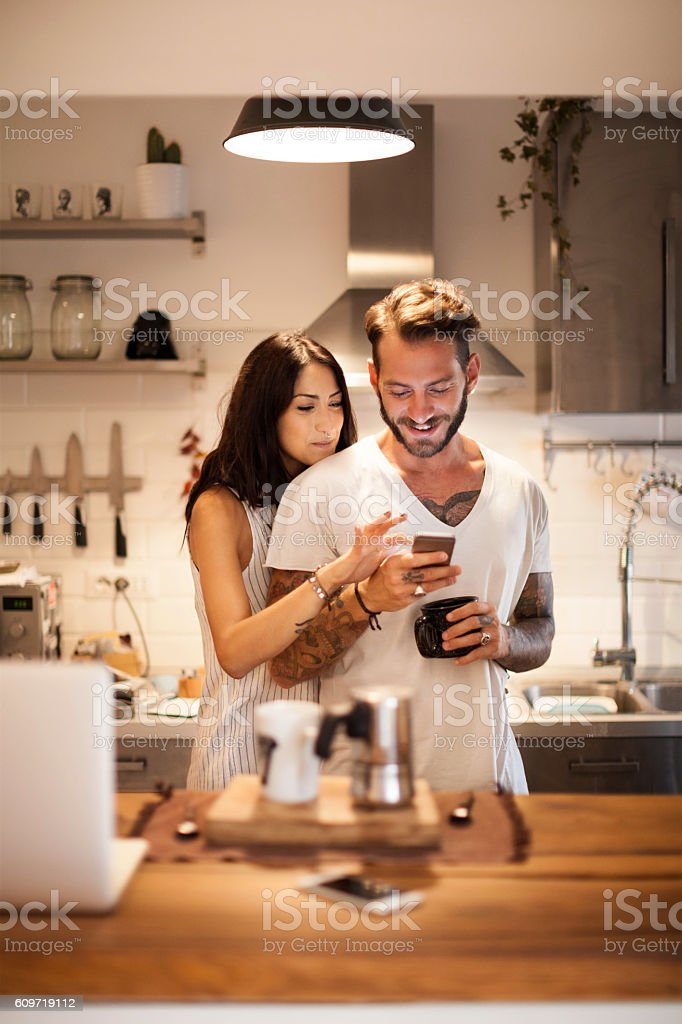 Young couple at home using smartphone - Morning breakfast time stock photo