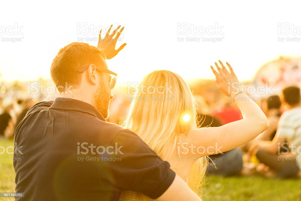 young couple at open air rock concert waving hands stock photo